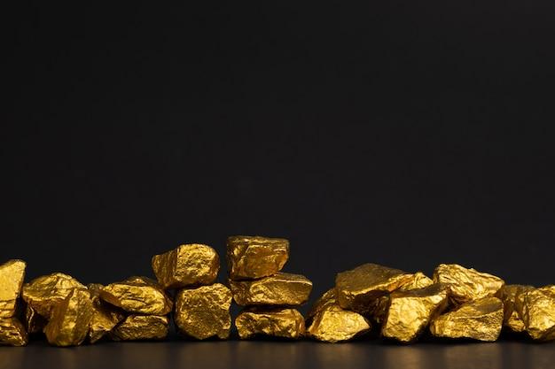 Een stapel goudklompjes of gouderts op zwart