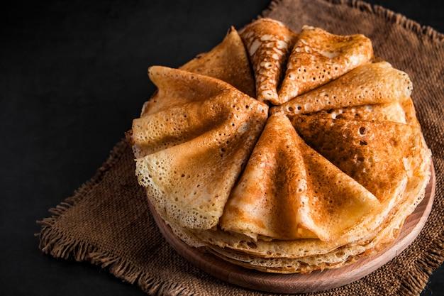 Een stapel heerlijke pannekoeken op een zwarte achtergrond sluit omhoog. voedsel voor de vakantie maslenitsa. plaats voor uw tekst.