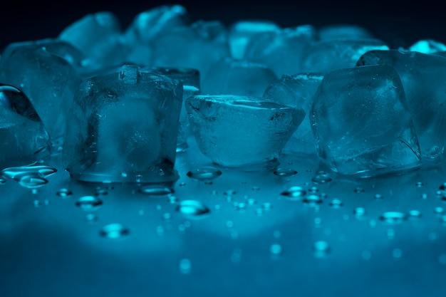 Een stapel ijsblokjes in turquoise kleur en druppels water op een reflecterende tafel