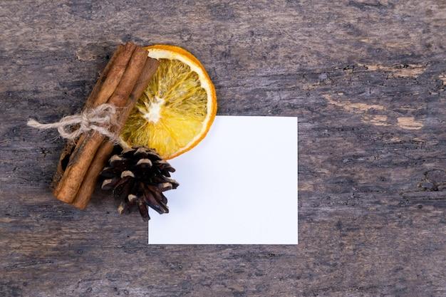 Een stapel kaneelstokjes, gedroogde sinaasappel, boomkegel en wit empy stuk papier met kopie ruimte. of brief