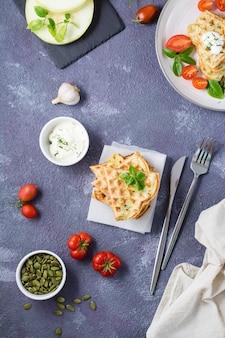 Een stapel kant-en-klare courgettewafels en basilicum op bakpapier op tafel. plantaardig dieet vegetarisch voedsel. boven- en verticaal aanzicht