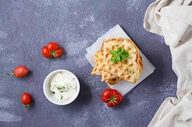 Een stapel kant-en-klare courgettewafels en basilicum op bakpapier op tafel. plantaardig dieet vegetarisch voedsel. bovenaanzicht. ruimte kopiëren