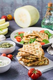Een stapel kant-en-klare courgettewafels en basilicum op bakpapier op tafel. plantaardig dieet vegetarisch voedsel. verticale weergave
