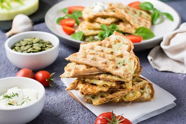 Een stapel kant-en-klare courgettewafels en basilicum op bakpapier op tafel. plantaardig dieet vegetarisch voedsel.