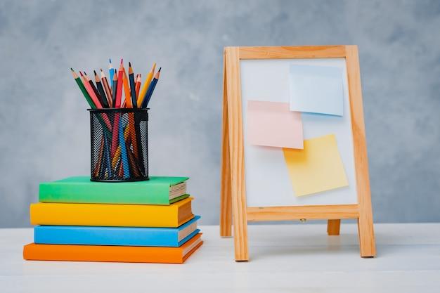 Een stapel kleurrijke leerboeken en een glas heldere potloden op een grijsblauwe achtergrond.