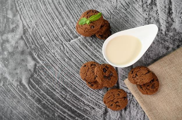 Een stapel koekjes en een lepel melk op een doek op een houten tafel