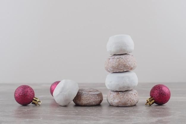 Een stapel koekjes en kerstballen gebundeld op marmer