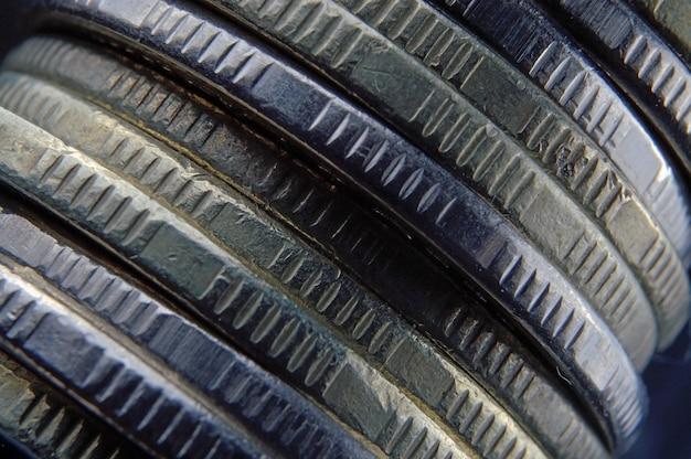 Een stapel munten valt op een donkere achtergrond. macrofoto.