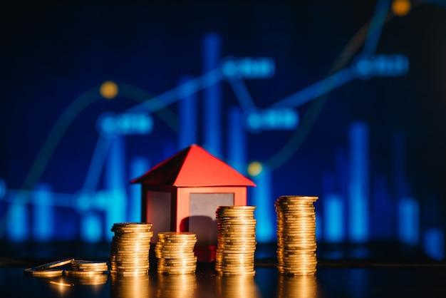 Een stapel muntstukken werpt een schaduw als huis, besparingsconcept