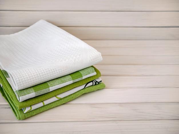 Een stapel netjes gevouwen handdoeken op een houten achtergrond. productie van natuurlijke textielvezels. biologisch product. natuurlijke materialen.