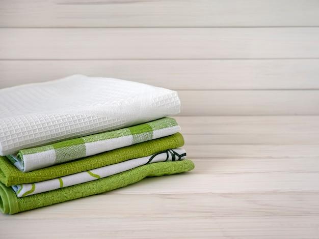 Een stapel netjes opgevouwen handdoeken van natuurlijke stoffen op een houten tafel
