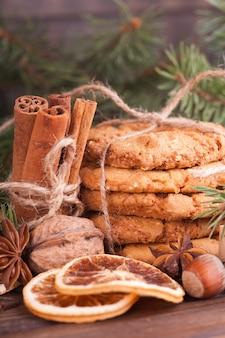 Een stapel notenkoekjes, kaneel, badon, sinaasappels, noten. feestelijke traktatie, kerstmis.