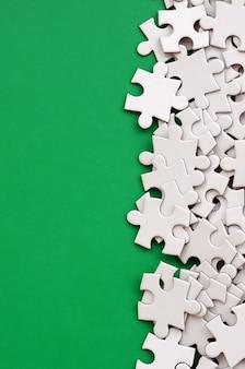 Een stapel ongekamde elementen van een witte legpuzzel ligt op een groen oppervlak