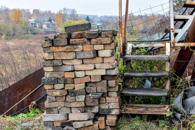 Een stapel oude bakstenen en een roestige trap