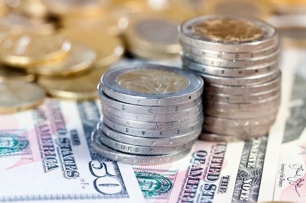 Een stapel oude, vuile en beschadigde munten van twee euro te midden van amerikaanse dollars en ander geld