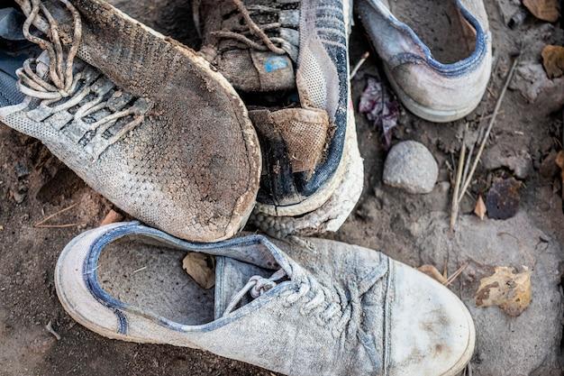 Een stapel oude vuile schoenen ligt op de grond. versleten schoenen. armoede en ellende concept.