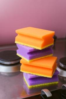 Een stapel paarse en oranje sponzen voor het wassen op het fornuis