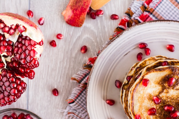 Een stapel pannenkoeken met granaatappel zaden op een bord