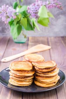 Een stapel pannenkoeken op een bord en een boeket lila in een vaas op een houten tafel