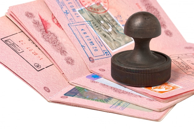 Een stapel paspoorten en stempel geïsoleerd op wit