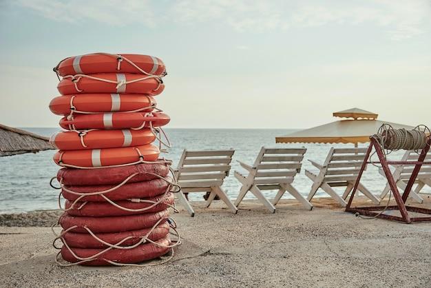 Een stapel reddingsboeien op het strand.