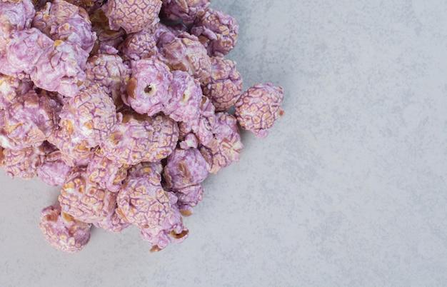 Een stapel snoep gecoate paarse popcorn op marmeren oppervlak