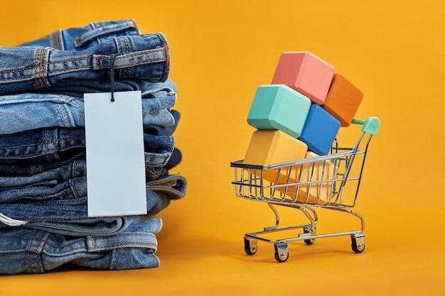 Een stapel spijkerbroek met een witte lege tag op een gele achtergrond. winkelwagentje met veelkleurige blokjes. verkoop woord geschreven op kubussen. verkoop concept. hoop stijlvolle trendy denim broek.