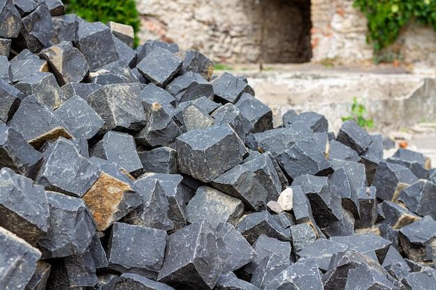Een stapel stenen van bouwmaterialen. stenen voor metselwerkbestrating en trottoir. het bouwen van granieten donkere keien.