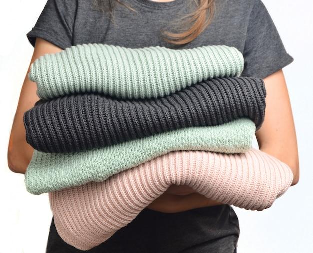 Een stapel sweaters in vrouwelijke handen die op witte achtergrond worden geïsoleerd.