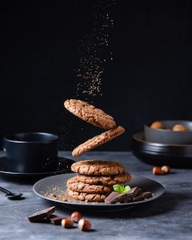 Een stapel vallende chocolate chip zelfgemaakte koekjes met chocoladeschilfers, noten en munt op een donkere tafel. vooraanzicht en kopieerruimte