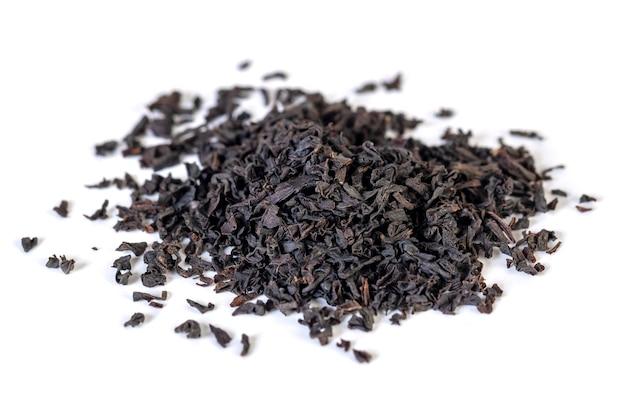 Een stapel van gedroogde zwarte theeblaadjes op een wit. energiek drankje.