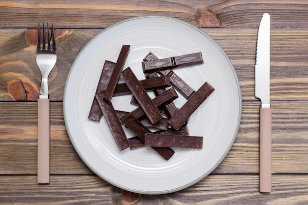 Een stapel van gevormde stukjes chocolade op een bord en bestek op een houten tafel. het concept van het eten van zoete tijd. bovenaanzicht