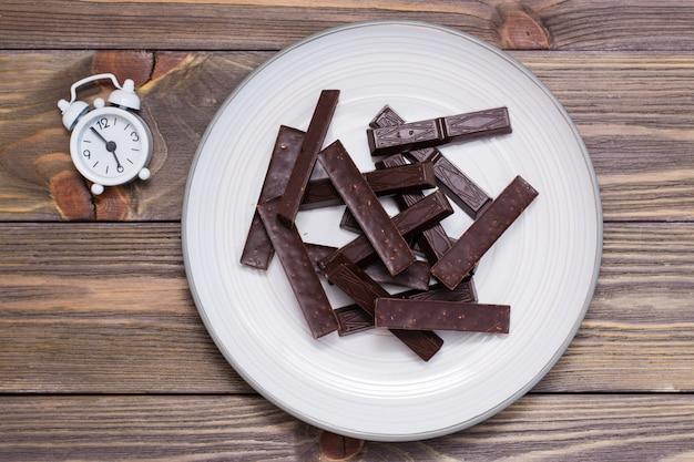 Een stapel van gevormde stukjes chocolade op een bord en een wekker op een houten tafel. het concept van het eten van zoete tijd. bovenaanzicht