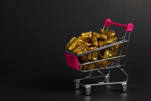 Een stapel van gouden goudklompjes of gouden erts in boodschappenwagentje of supermarktkarretje op zwarte achtergrond