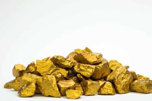 Een stapel van goudklompjes of gouden erts dat op witte achtergrond, edelsteen of stuk van gouden steen, financieel en bedrijfsconcept wordt geïsoleerd.