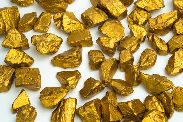Een stapel van goudklompjes of gouden erts op witte achtergrond,