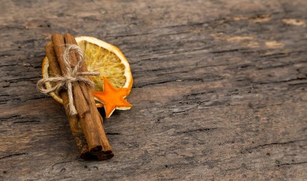 Een stapel van kaneelstokjes, gedroogde sinaasappel en mandarijn sterren op oude houten tafel met kopie ruimte. kerst decoratie. kerstkaart