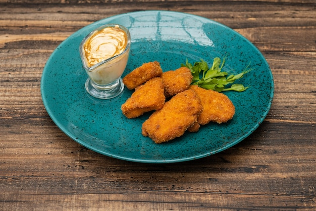 Een stapel van kipnuggets op blauw bord met saus en groen