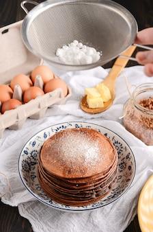 Een stapel van pannekoeken met een houten lepel boter, eieren, op een rustieke houten lijst.