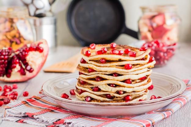 Een stapel van pannekoeken met granaatappelzaden op een plaat