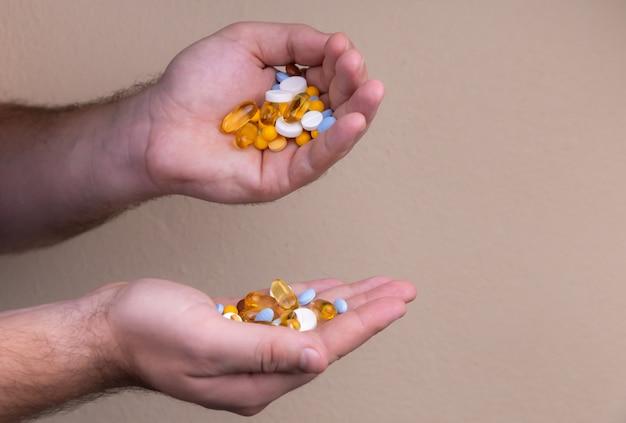 Een stapel veelkleurige pillen in een mannelijke hand.