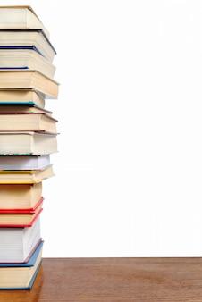 Een stapel verschillende boeken op een tafel tegen