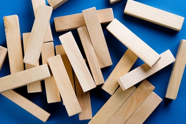 Een stapel verspreide houten blokken op een blauwe achtergrond. constructiespel. de gebroken toren.
