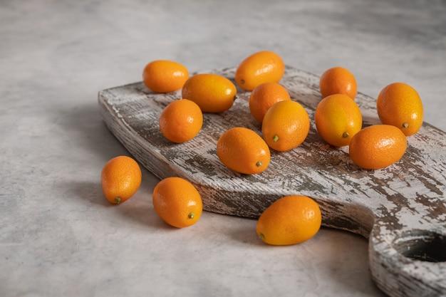 Een stapel vitamine kumquat-vruchten op het oude houten bord op grijs