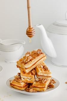 Een stapel wafels met honing en walnoten op witte achtergrond
