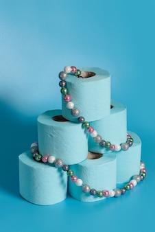 Een stapel wc-papier, versierd met een kerstboomkrans.