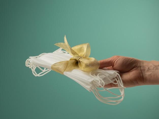 Een stapel witte medische maskers vastgebonden met een gele strik ligt op een hand als een geschenk a
