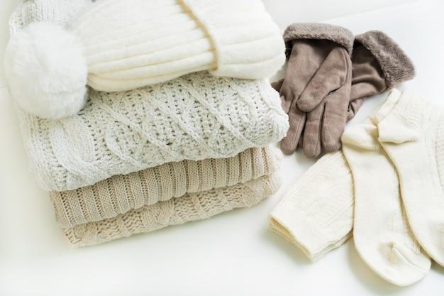 Een stapel wollen trui, hoed, handschoen en sok, warme kleding. huiselijke sfeer, winterkleding. warm en gezellig. gebreide kleding. gezellige sfeer. , detailopname
