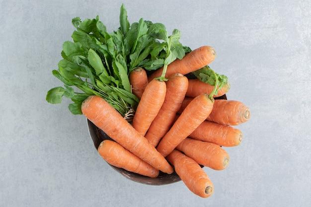 Een stapel wortelen in de kom, op het marmer.