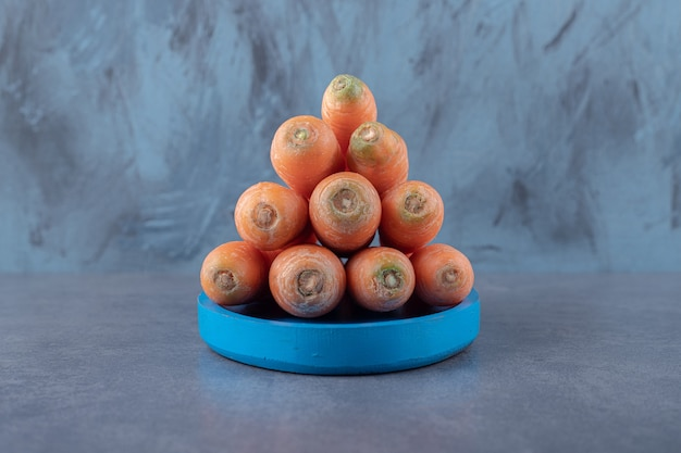 Een stapel wortelen op het blauwe dienblad, op het marmeren oppervlak.